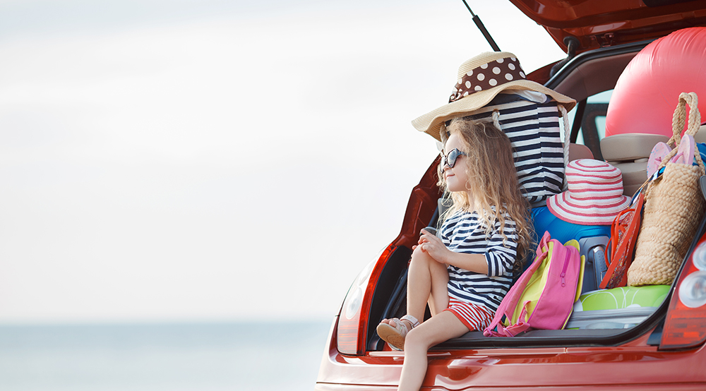 Girl sitting in the open boot of a car at the beach