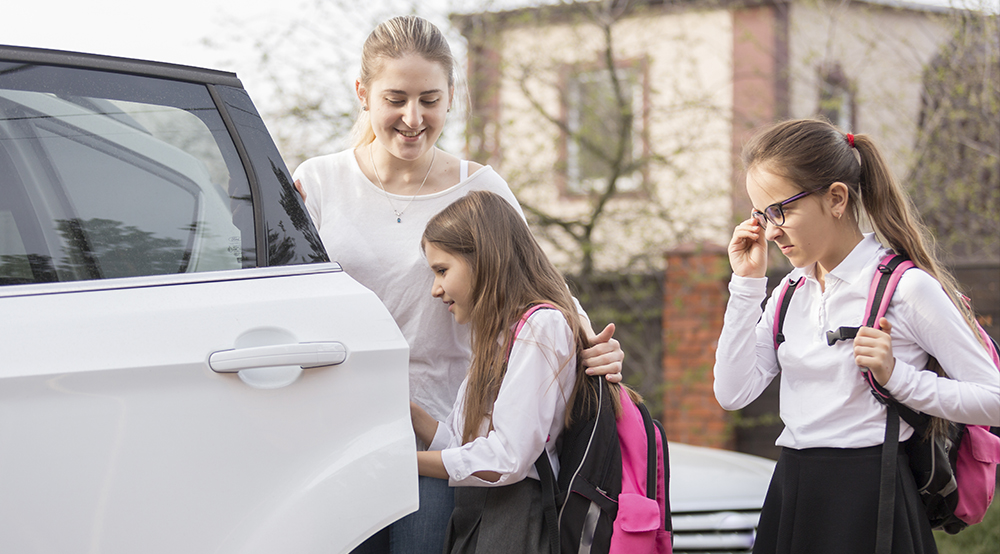 Mother taking her daughters to school