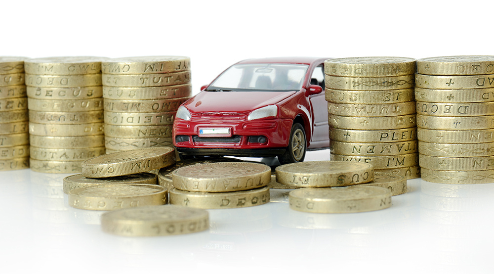 A red toy car surrounded by pound coins