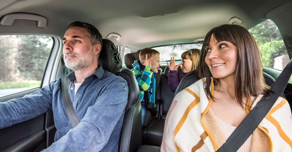 Family of four in a car with the children pulling faces in the back seats