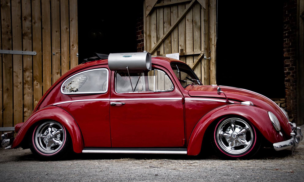 A red Volkswagen Beetle against a wooden background