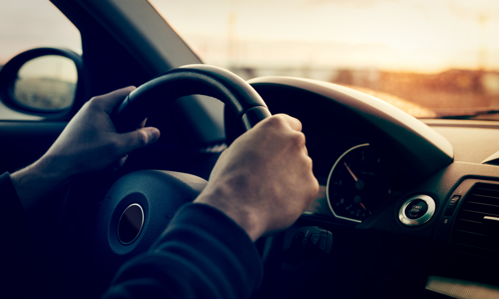 Driving a car at sunset - focus on steering wheel