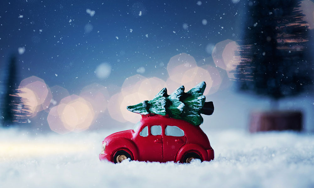 Driving home for Christmas, mini retro car with faux Christmas tree on top