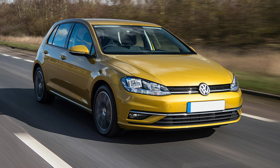 Gold Volkswagen Golf driving down a road