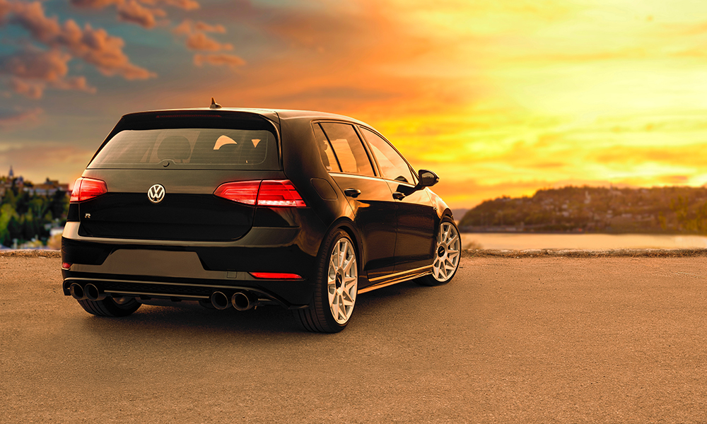The back of a black Volkswagen Golf R, on a road at the top of a hill, against a yellow sunset