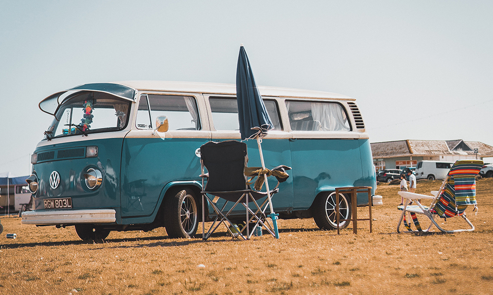 Blue Volkswagen Campervan parked on a beach, with a parasol and deckchairs. Against a blue sky.