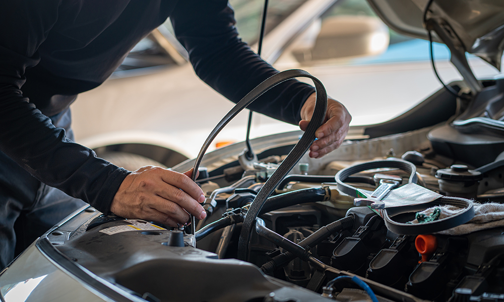 Mechanic holding the timing belt of a car